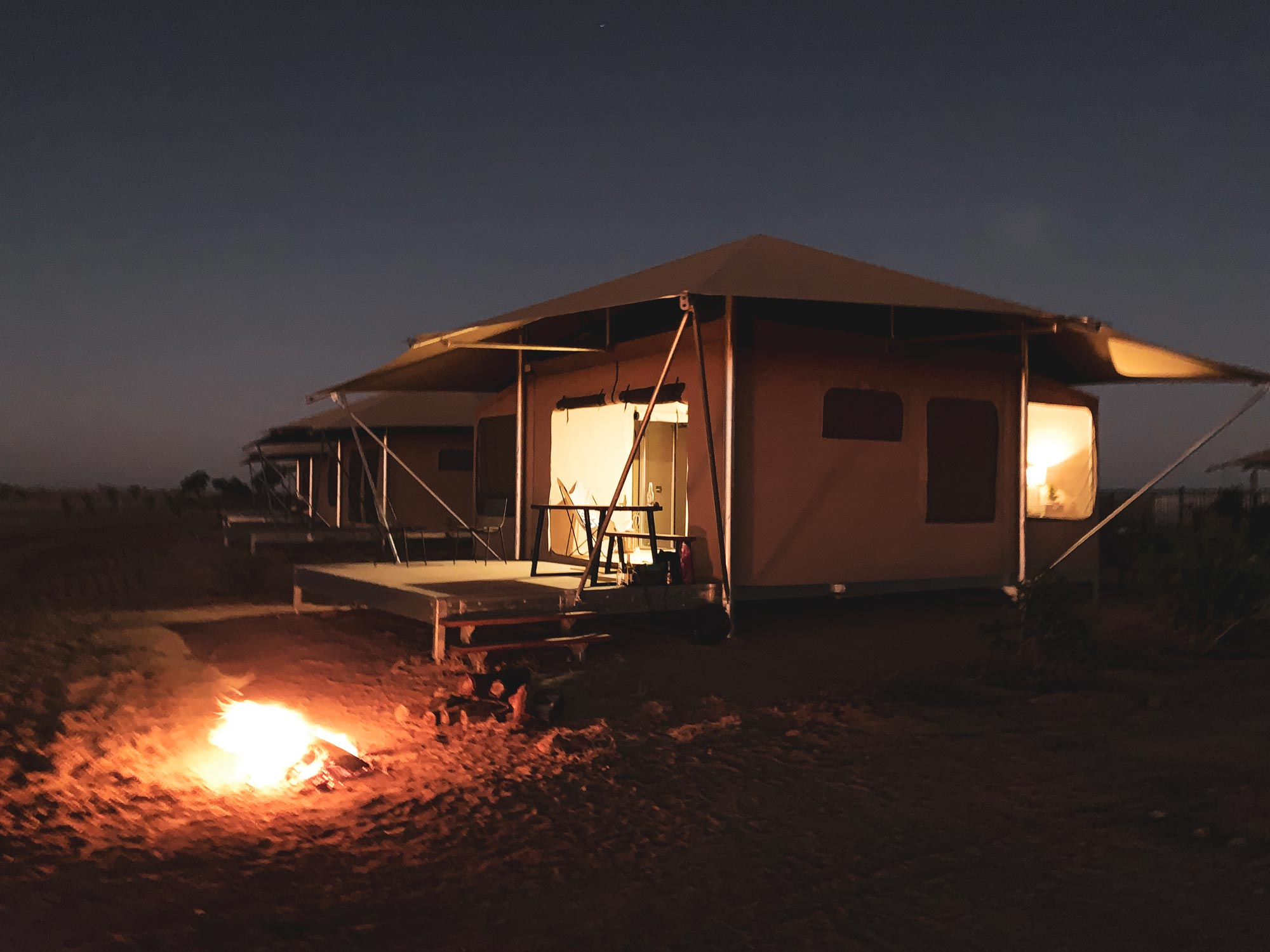 Glamping tent at night with fire pit
