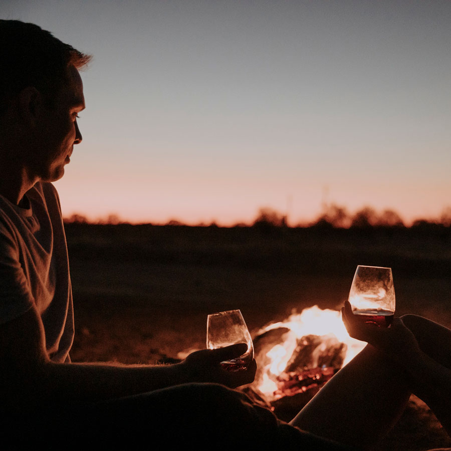 Couple sitting by fire pit with glass of wine